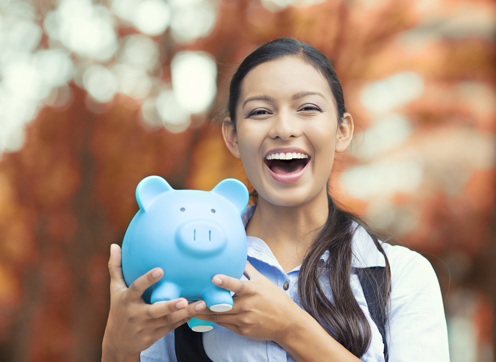 smiling business woman holding piggy bank