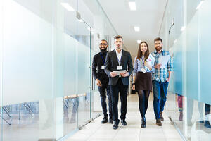Full length of group of happy youngbusiness people walking the corridor in office together