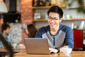 Happy man using laptop in cafe